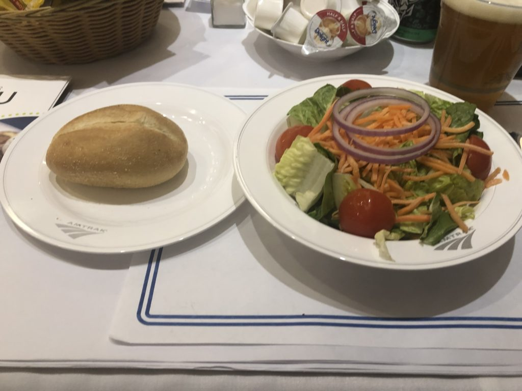 Amtrak's salad and dinner roll in a traditional Amtrak dining car