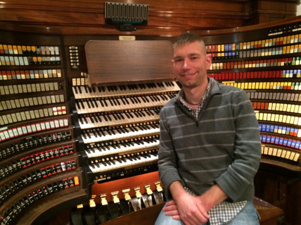 Kev sitting at a large organ console.